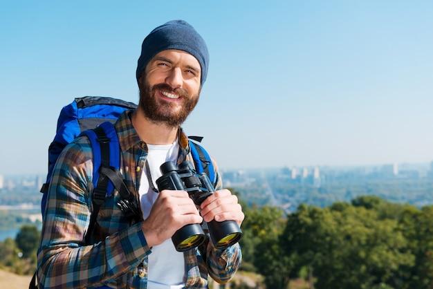 Goed landschap. knappe jonge man die rugzak draagt en met een glimlach naar de camera kijkt terwijl hij in de natuur staat en een verrekijker vasthoudt