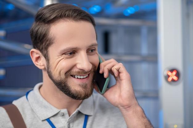 Goed nieuws. close-up lachend gezicht van gelukkige jonge volwassen man praten over smartphone