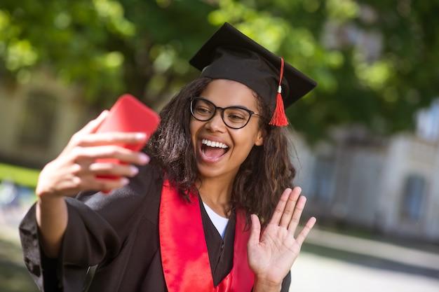 Goed nieuws delen. jonge afgestudeerde voelt zich gelukkig en opgewonden tijdens een videogesprek
