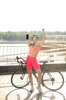 Goed nieuws. een meisje met een fiets die bij de brug staat met een smartphone in handen