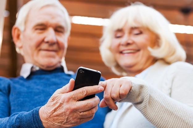 Goed nieuws. gelukkig senior koppel hecht zich aan elkaar en glimlacht terwijl ze buiten staan en naar de mobiele telefoon kijken
