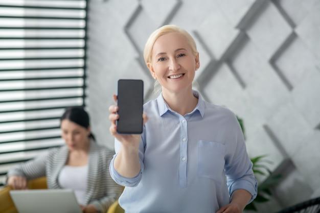 Goed nieuws. glimlachende volwassen vrouw die zich in ruimte bevindt die het smartphonescherm toont, donkerharig met laptop.