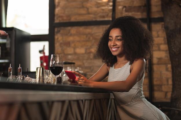 Goed nieuws. kleine gekrulde vrouw zit aan de bar en glimlacht gelukkig nadat ze een bericht met goed nieuws op haar smartphone heeft ontvangen