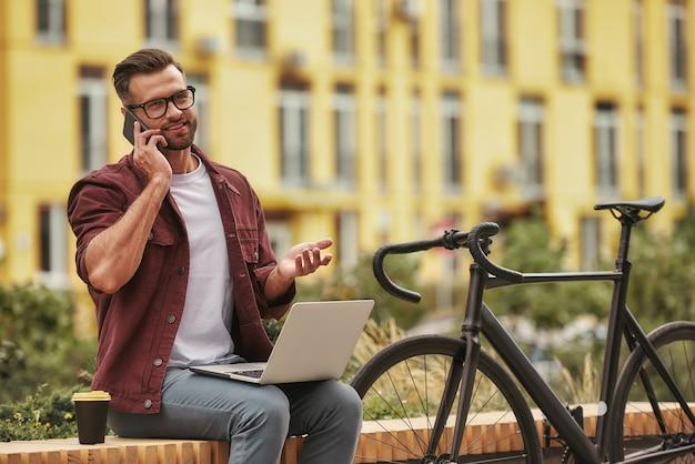 Goed nieuws knappe en jonge man met stoppels in casual kleding die op laptop werkt en