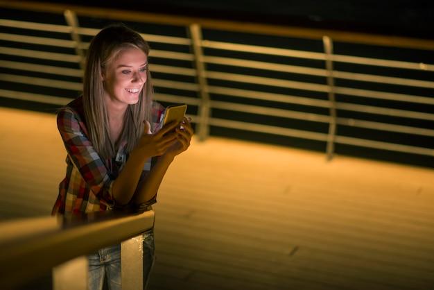 Goed nieuws. mooi jong meisje controleert iets op haar slimme telefoon en glimlacht afwezig.
