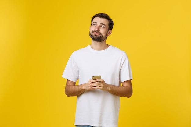 Goed nieuws van vriend. zekere jonge knappe mens die in jeansoverhemd slimme telefoon houden tegen geel