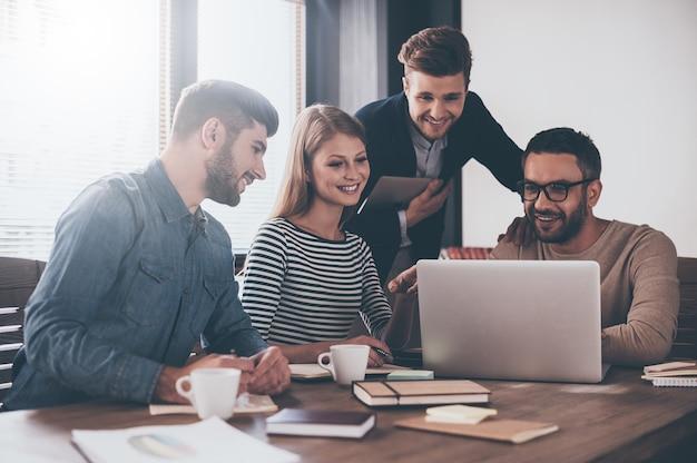 Goed nieuws voor ons. jonge knappe man die met een glimlach naar een laptop kijkt terwijl hij aan de kantoortafel zit op een zakelijke bijeenkomst met zijn collega's