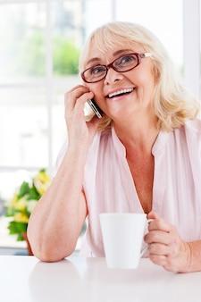 Goed nieuws. vrolijke senior vrouw die op de mobiele telefoon praat en glimlacht terwijl ze aan tafel zit