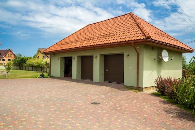 Goed onderhouden omheind terrein. nieuwe vrijstaande garage voor drie auto's met schotelantenne op rood schindeldak, brede automatische deuren op grote schone ruime verharde tuin. vastgoed en welvaart concept.