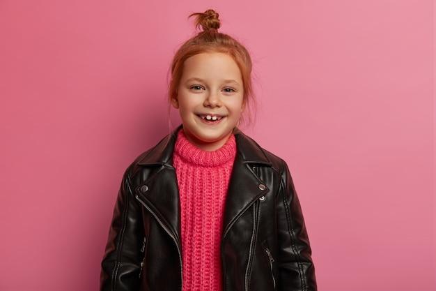 Goed uitziend positief klein kind heeft roodgekamd haar in de knoop, draagt een roze gebreide trui en een leren zwart jasje, voelt zich speels, blij na een geslaagde winkeldag, staat tegen een roze muur.