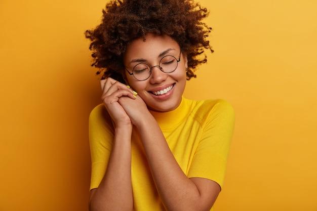 Goed uitziend teder jong vrouwelijk model leunt naar de handen, lacht teder, sluit de ogen en stelt zich iets geweldigs of plezierigs voor, aangeraakt worden, draagt een bril en een gele outfit, heeft een romantische bui