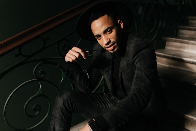 Goed uitziende afrikaanse man zittend op de trap en op zoek. moe man in jas poseren op trappen.