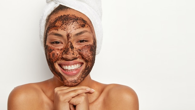 Goed uitziende afro-amerikaanse vrouw houdt de handen tegen elkaar gedrukt, voelt plezier en vreugde, kijkt vrolijk naar zichzelf in de spiegel, draagt een zachte handdoek om het hoofd gewikkeld, reinigt het gezicht met een schoonheidsmasker.