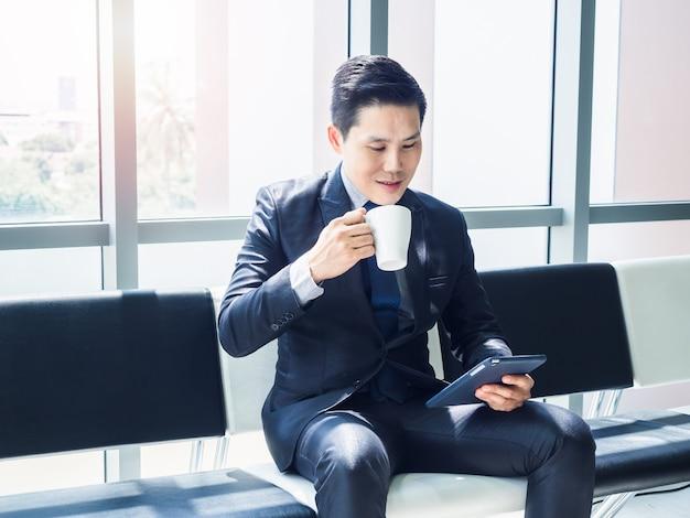 Goed uitziende aziatische zakenman in pak kijken naar tablet op zijn hand en witte kop warme koffie drinken zittend op wachtstoel