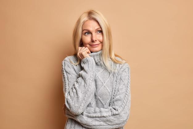 Goed uitziende blonde volwassen europese vrouw staat in bedachtzame houding draagt comfortabele grijze trui geconcentreerd opzij overdenkt bij het maken van een keuze.