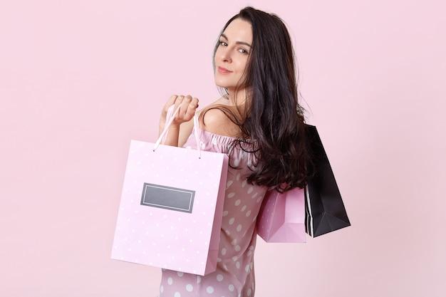 Goed uitziende brunette vrouw staat zijwaarts, houdt boodschappentassen, keert terug uit winkelcentrum met een goed humeur, poseert op roze. vrouwen en inkoopconcept.