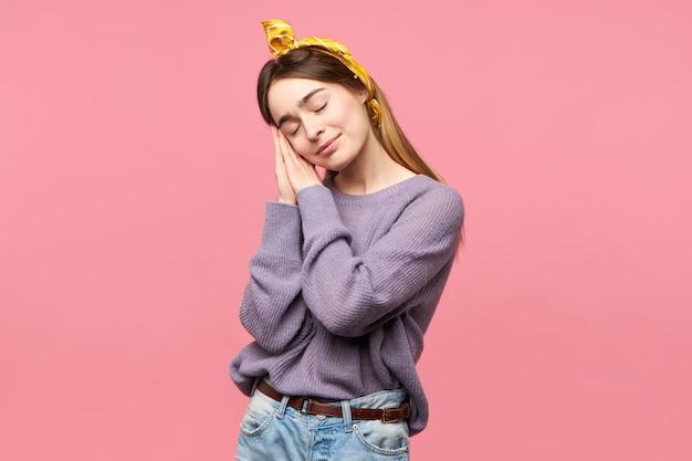 Goed uitziende charmante jonge vrouw met zijden sjaal op haar hoofd ogen gesloten en glimlachend houden