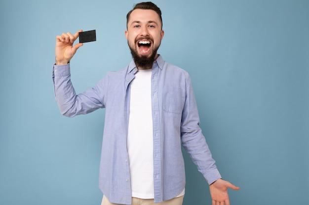 Goed uitziende coole dolblij lachende brunette bebaarde jonge man met stijlvol blauw shirt en wit t-shirt geïsoleerd over blauwe achtergrond muur met creditcard camera kijken en plezier hebben.