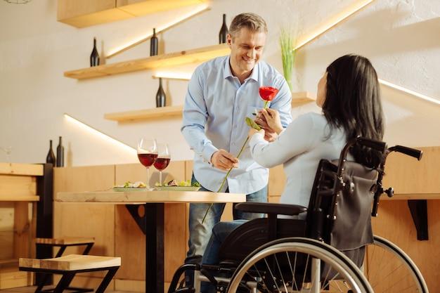 Goed uitziende geïnspireerde blonde man die lacht en een rode bloem geeft aan zijn geliefde donkerharige gehandicapte vrouw tijdens een romantisch diner