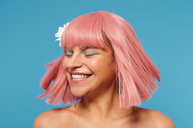 Goed uitziende gelukkige jonge romantische dame met kort roze kapsel, zwaaiend met haar haren en vrolijk lachend met gesloten ogen, staande met blote schouders