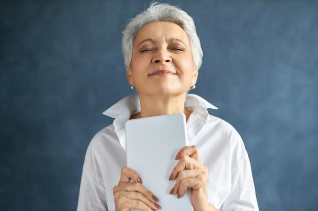 Goed uitziende grijze haren rijpe zakenvrouw ogen sluiten met plezier, met gelukkige uitdrukking