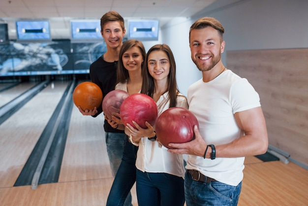 Goed uitziende jeugd. vrolijke vrienden vermaken zich in het weekend in de bowlingclub