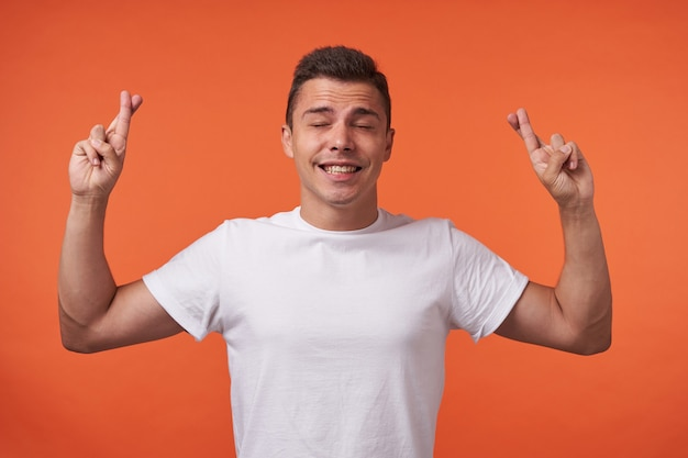 Goed uitziende jonge aantrekkelijke bruinharige man in wit t-shirt lachend met gesloten ogen en het verhogen van handen met gekruiste vingers, die zich voordeed op oranje achtergrond