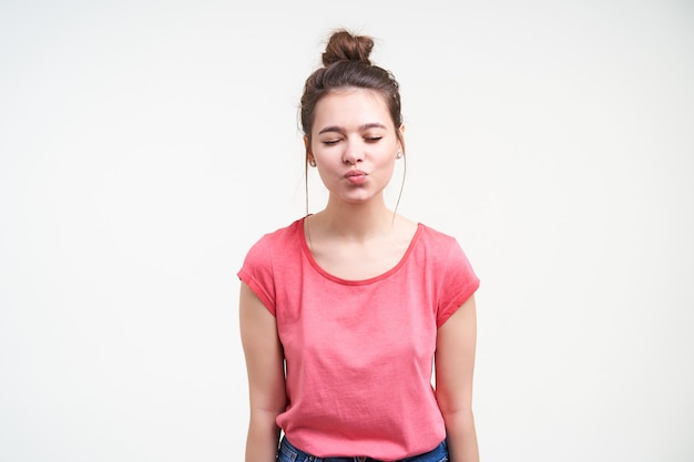Goed uitziende jonge charmante bruinharige vrouw met natuurlijke make-up haar ogen dicht te houden tijdens het vouwen van lippen in lucht kus, geïsoleerd op witte achtergrond