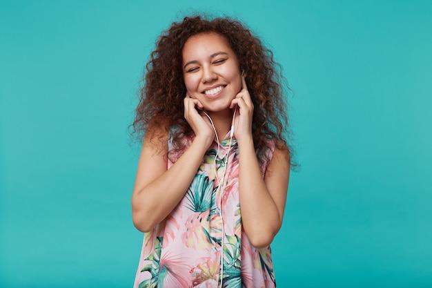 Goed uitziende jonge krullende brunette dame met casual kapsel haar ogen dicht houden en graag glimlachen terwijl ze geniet van muzieknummer, staande op blauw