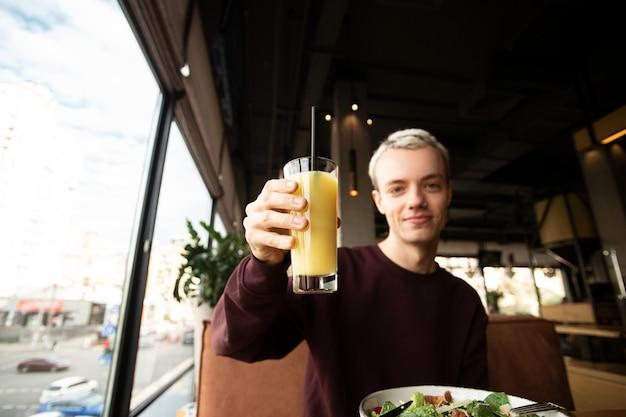 Goed uitziende jonge man zit in een café in de buurt van een panoramisch raam. hij heeft een glas sinaasappelsap in zijn hand