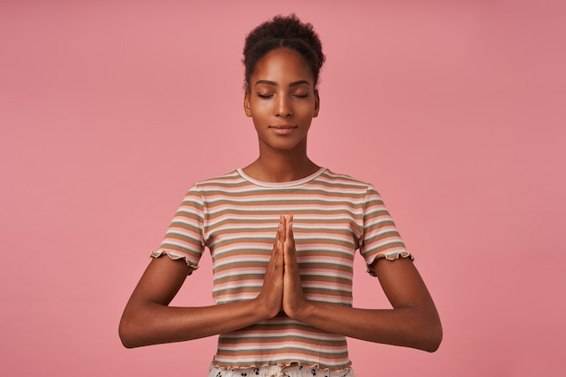 Goed uitziende jonge mooie bruinharige krullende vrouw met knot kapsel handen samen vouwen tijdens het mediteren met gesloten ogen, geïsoleerd over roze muur