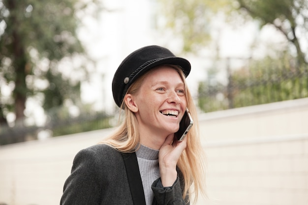 Goed uitziende jonge positieve blonde dame in trendy kleding vrolijk lachen terwijl ze aangenaam praten op haar telefoon, vrienden ontmoeten en in een goede bui zijn