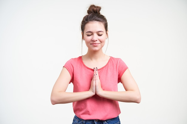 Goed uitziende jonge positieve bruinharige vrouw die opgeheven handpalmen bij elkaar houdt en zachtjes glimlacht met gesloten ogen, staande op een witte achtergrond in vrijetijdskleding