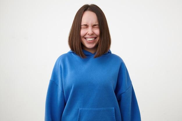 Goed uitziende jonge vrij kortharige brunette vrouw gekleed in blauwe hoodie glimlachend vrolijk met gesloten ogen terwijl staande over witte muur