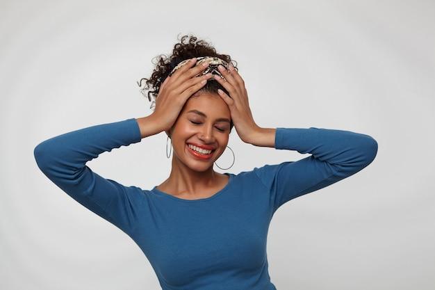 Goed uitziende jonge vrolijke donkerharige krullende vrouw die wijd met gesloten ogen glimlacht en opgeheven handen op haar hoofd houdt, die zich over witte achtergrond bevindt