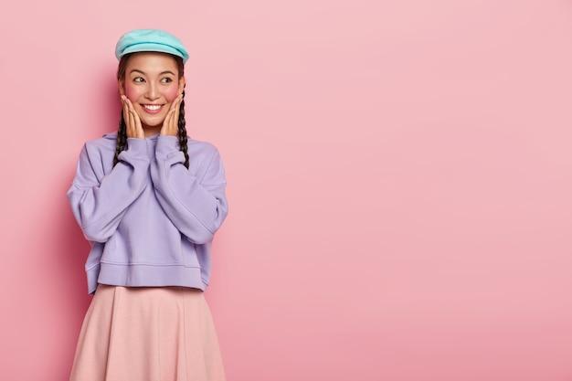 Goed uitziende jonge vrouw met aantrekkelijke uitstraling, raakt beide wangen aan, kijkt opzij, draagt blauwe pet, paarse losse trui en rok, stelt zich voor dat er in de toekomst iets leuks is gebeurd