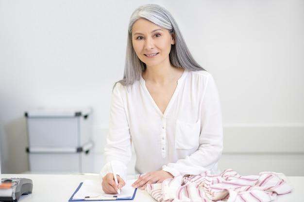 Goed uitziende lachende vrouw met lang grijs haar kleren chemisch reinigen schrijven achter de toonbank nemen