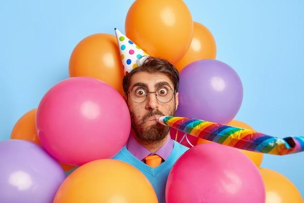 Goed uitziende man omringd door partij ballonnen poseren