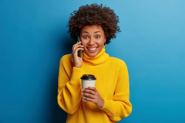 Goed uitziende positieve afro-amerikaanse vrouw heeft telefoongesprek, houdt mobiele telefoon in de buurt van oor