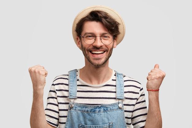 Goed uitziende, positieve mannelijke boer steekt gebalde vuisten op, voelt zich tevreden en opgewonden, behaalt groot succes op landbouwgebied, draagt casual overall, gestreepte trui, strooien hoed, heeft een brede glimlach