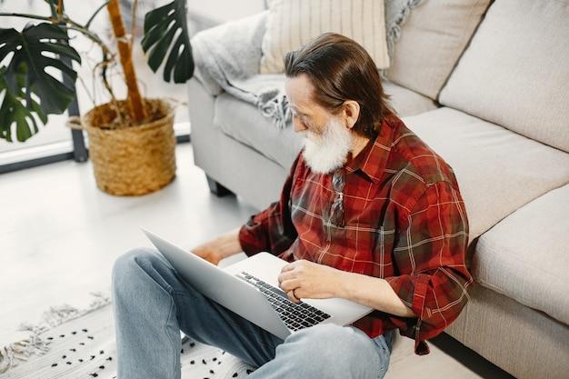 Goed uitziende senior man. werken met laptop. op de vloer zitten. fastfood eten.