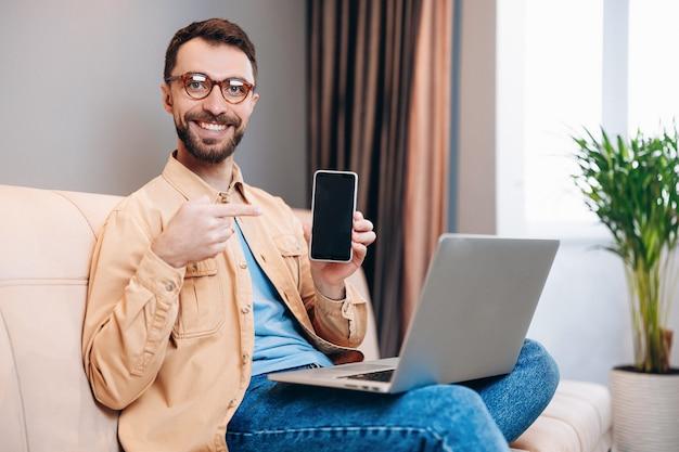 Goed uitziende slimme man met een stralende glimlach houdt smartphone in de ene hand en wijst ernaar met een andere
