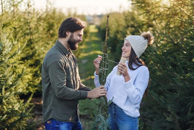 Goed uitziende stijlvolle glimlachende jonge paar banden met draden mooie kerstboom gekocht bij speciale plantplaats.
