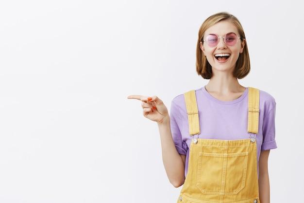 Goed uitziende stijlvolle jonge vrouw in zonnebril glimlachen, promo aanbevelen, wijzende vinger links naar copyspace