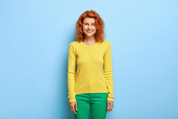 Goed uitziende vriendelijke vrolijke vrouw met golvend rood haar