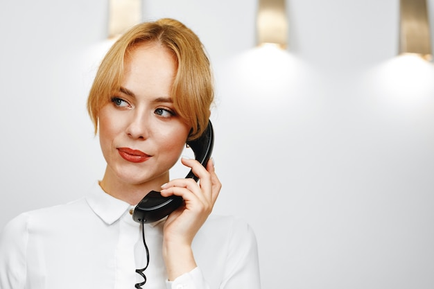 Goed uitziende vriendelijke vrouw hotelreceptionist praten aan de telefoon close-up