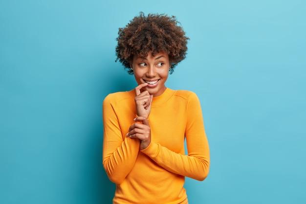 Goed uitziende vrolijke afro-amerikaanse vrouw glimlacht zachtjes draagt casual trui met lange mouwen kijkt vreugdevolle opzij poses tegen blauwe muur