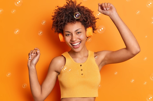Goed uitziende, vrolijke vrouw danst zorgeloos houdt de armen omhoog draagt een stereohoofdtelefoon op de oren beweegt met het ritme van de muziek glimlacht breed geïsoleerd over levendige oranje muur