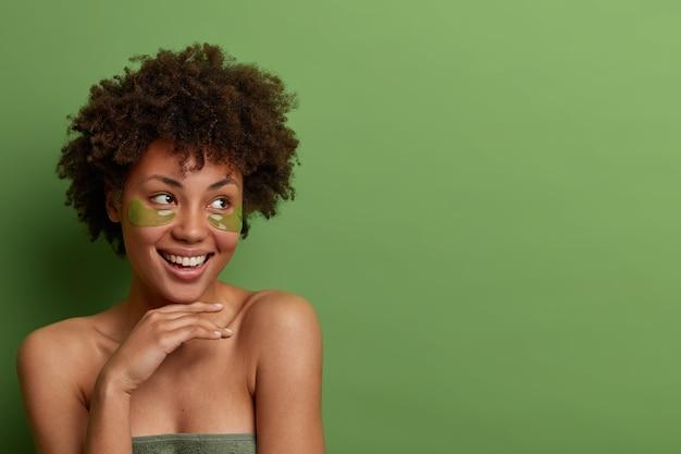 Goed uitziende, vrolijke vrouw houdt de hand zachtjes onder de kin, kijkt bedachtzaam opzij, draagt hydrogel-ooglapjes voor een gezonde, frisse huid, gewikkeld in een handdoek, geïsoleerd op groene muur, kopieer ruimte voor tekst