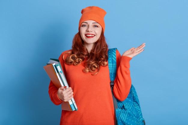 Goed uitziende vrolijke vrouw met rood golvend haar, gekleed in een nonchalante oranje trui en pet